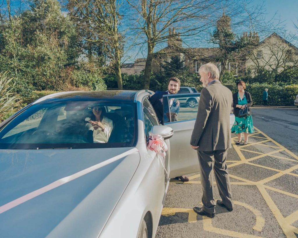 Groom in car after wedding ceremony
